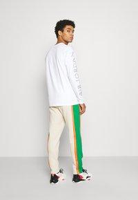 Jordan - PANT - Pantalon de survêtement - oatmeal/lucky green/track red - 2
