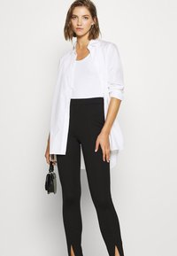 NA-KD - FRONT SLIT PANTS - Trousers - black - 3