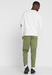 Puma - ENERGY PANT - Pantalon de survêtement - olivine/yellow - 2