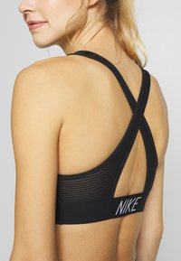 Nike Performance - BRA PAD - Medium support sports bra - black/white - 5