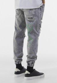 Bershka - MIT PRINT UND ZIERRISSEN  - Jeans Tapered Fit - grey - 2