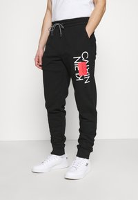 Calvin Klein - TEXT REVERSED  - Tracksuit bottoms - black - 0
