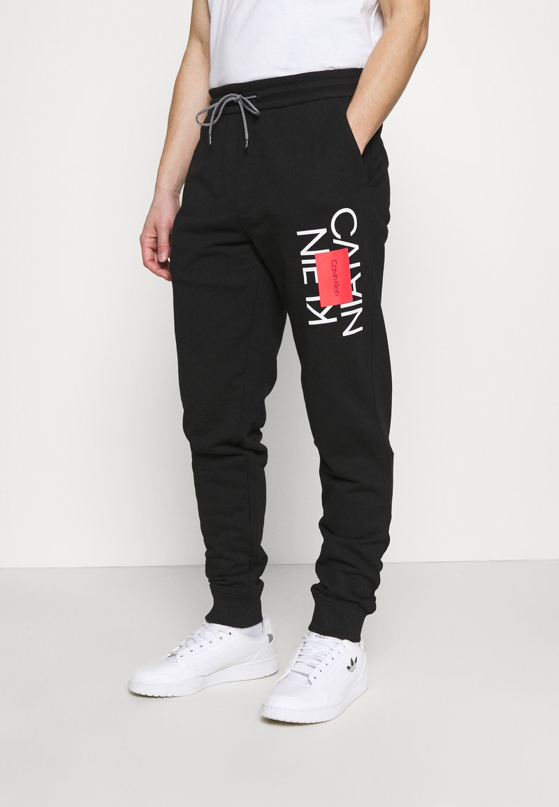 Calvin Klein - TEXT REVERSED  - Tracksuit bottoms - black