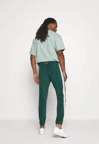 WRSTBHVR - TRACKPANTS LOUNGIN - Tracksuit bottoms - green/off white - 2