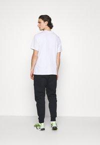 Nike Sportswear - Tracksuit bottoms - black/volt - 2