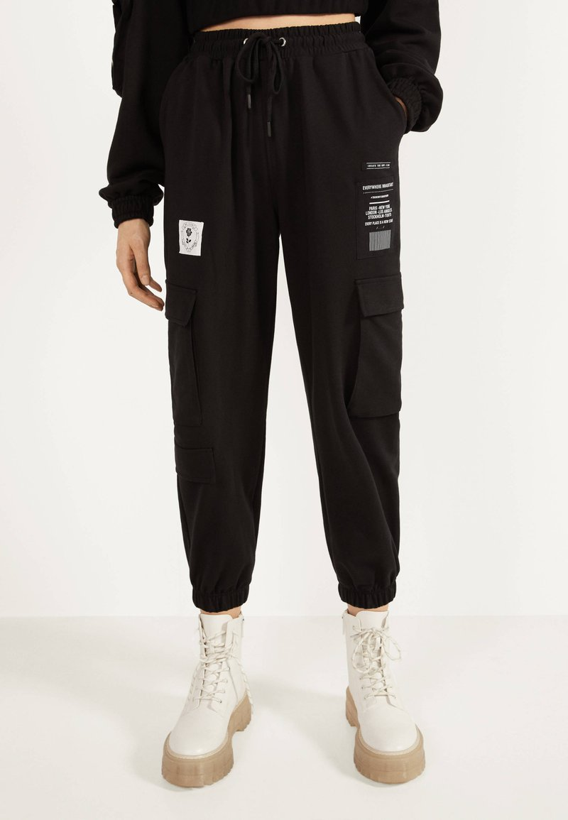 Bershka - IM CARGOSTIL AUS PLÜSCHGEWEBE  - Teplákové kalhoty - black