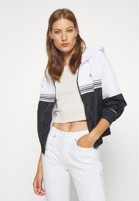Calvin Klein Jeans - STRIPE TAPE HOODED WINDBREAKER - Summer jacket - black - 3