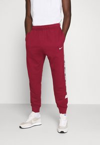 Nike Sportswear - REPEAT  - Tracksuit bottoms - team red - 0