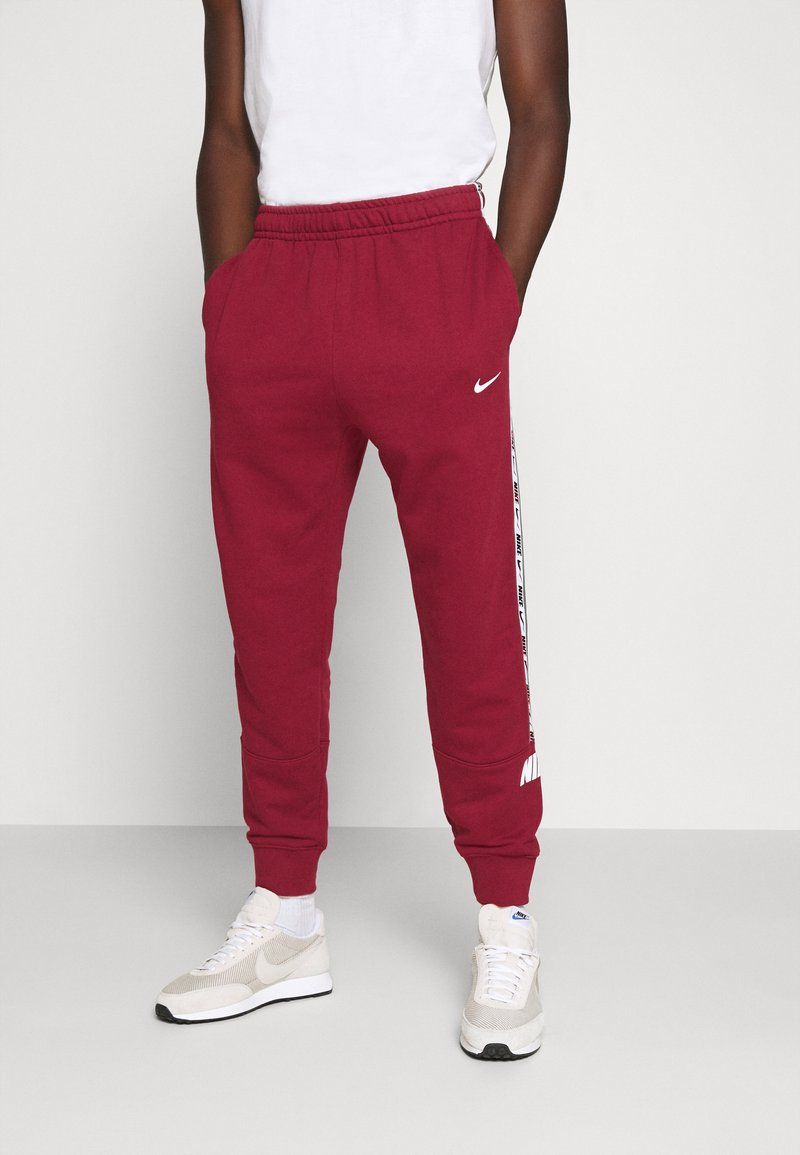 Nike Sportswear - REPEAT  - Tracksuit bottoms - team red