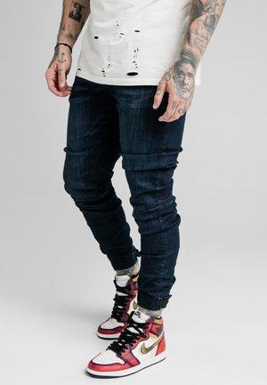ELASTICATED STRAP CUFF - Jeans slim fit - midstone
