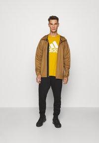 adidas Performance - ESSENTIALS SPORTS SHORT SLEEVE TEE - Print T-shirt - legacy gold - 1