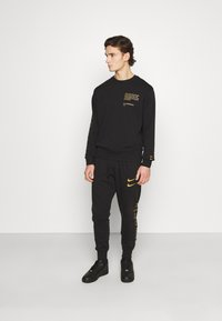 Nike Sportswear - PANT - Tracksuit bottoms - black/gold foil - 1