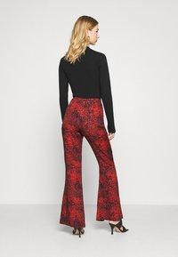 Milk it - TROUSER FRONT SPLIT DETAIL - Trousers - red/black - 2