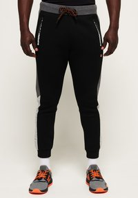 Superdry - MIT FARBBLOCK-DESIGN - Tracksuit bottoms - black - 0
