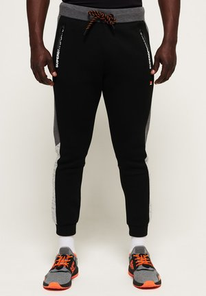 MIT FARBBLOCK-DESIGN - Tracksuit bottoms - black