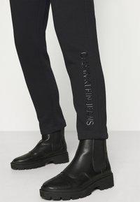 Calvin Klein Jeans - SHINY RAISED PANT - Tracksuit bottoms - black - 3