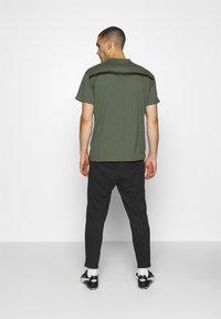 Puma - CASUALS PANT - Pantalon de survêtement - black/fizzy orange - 2