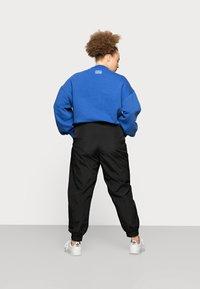 Pieces Curve - PCGOIA TRACK PANT - Tracksuit bottoms - black - 2