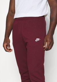 Nike Sportswear - CLUB - Tracksuit bottoms - dark beetroot/white - 4
