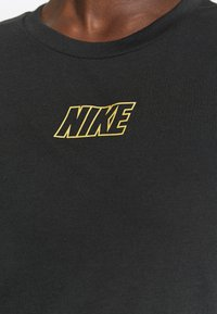 Nike Performance - DRY TIE - Print T-shirt - black/metallic gold - 7