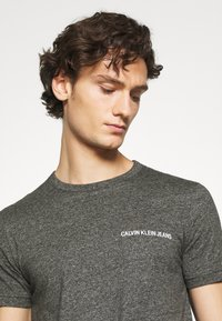 Calvin Klein Jeans - INSTITUTIONAL CHEST GRINDLE TEE - T-shirt med print - black - 4