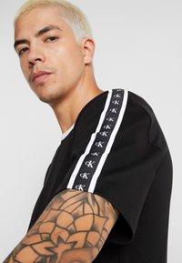 Calvin Klein Jeans - MONOGRAM TAPE TEE - T-shirt imprimé - black beauty/white tape - 4