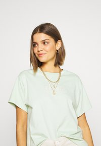 Levi's® - GRAPHIC VARSITY TEE - T-shirts med print - light green - 3