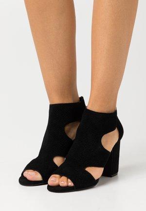 HELLI - Ankle cuff sandals - black