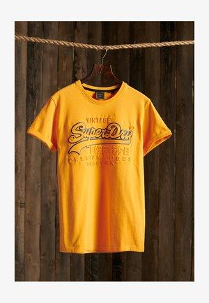 VINTAGE LOGO EMBOSSED - T-shirt med print - alaska gold