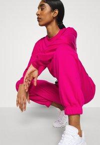 Nike Sportswear - Tracksuit bottoms - fireberry/black/white - 4