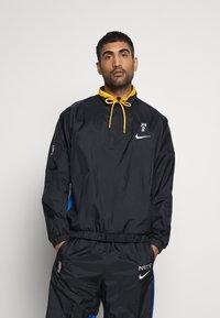 Nike Performance - NBA BROOKLYN NETS CITY EDITION TRACKSUIT - Tracksuit - black/royal blue/university gold - 0