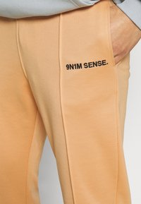 9N1M SENSE - LOGO PANTS UNISEX - Tracksuit bottoms - apricot/black - 4