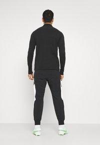 Nike Performance - FC PANT - Tracksuit bottoms - black/white/saturn gold - 2