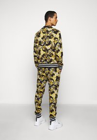 Versace Jeans Couture - FLEECE NEW LOGO - Tracksuit bottoms - nero - 2