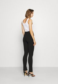 NA-KD - FRONT SLIT PANTS - Trousers - black - 2