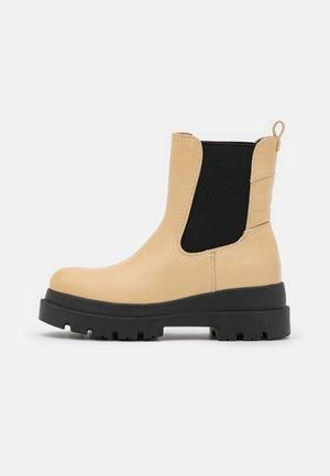 ESSIEE - Platform ankle boots - dark yellow