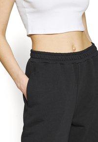 NA-KD - NA-KD X ZALANDO EXCLUSIVE - LOOSE FIT PANTS - Tracksuit bottoms - black - 4