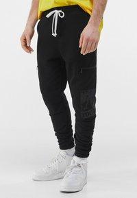 Bershka - MIT PRINT UND TASCHEN  - Pantaloni sportivi - black - 0