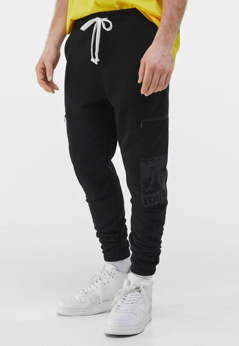 Bershka - MIT PRINT UND TASCHEN  - Pantaloni sportivi - black