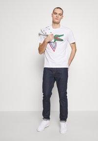 Lacoste - Unisex Lacoste x Jean-Michel Tixier Design Cotton T-shirt - T-shirts med print - blanc/rouge - 1