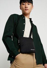 Calvin Klein Jeans - MONOGRAM MICRO FLATPACK - Sac bandoulière - black - 1