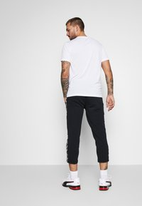 Puma - AMPLIFIED PANTS - Tracksuit bottoms - black - 2