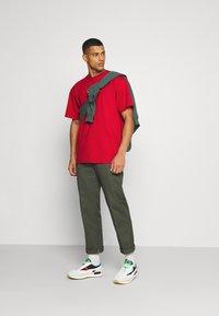 Karl Kani - SMALL SIGNATURE TEE UNISEX - Print T-shirt - dark red - 1