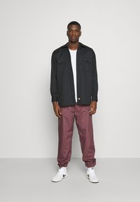 Carhartt WIP - ALISTAIR PANT - Tracksuit bottoms - black/etna red - 1