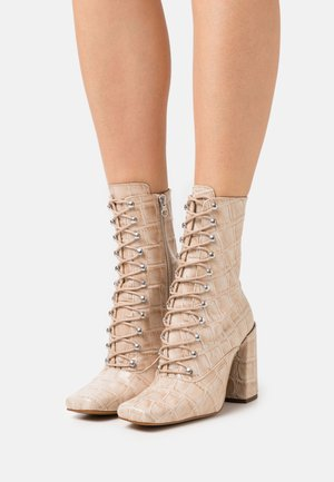 High heeled boots - natural