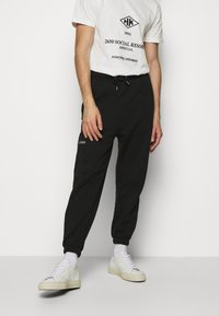 Han Kjøbenhavn - PANTS - Tracksuit bottoms - black - 0