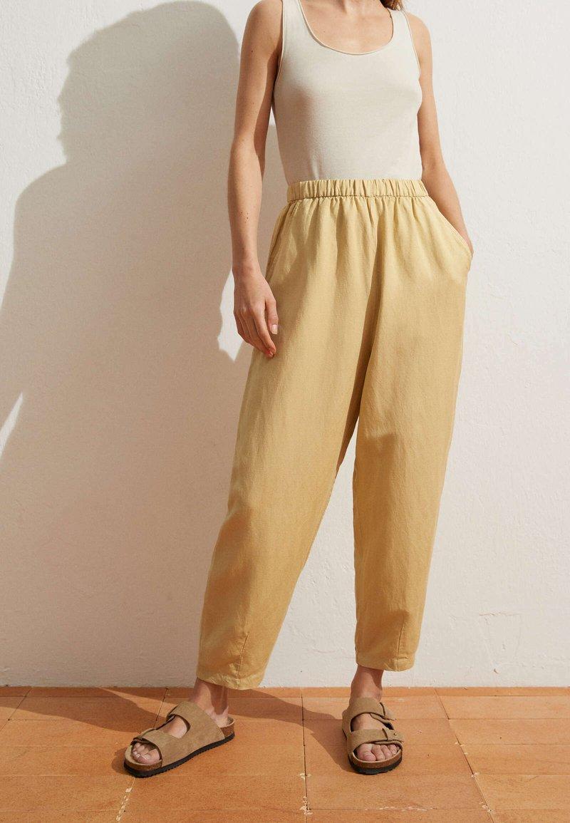 OYSHO - MIT LEINENANTEIL - Trousers - light yellow