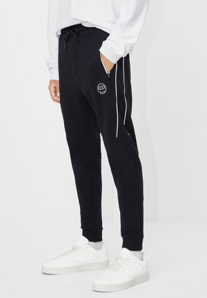 REFLEKTIERENDE - Tracksuit bottoms - black
