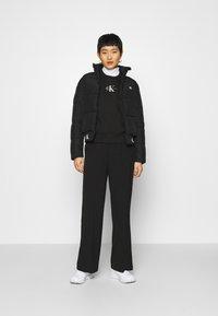 Calvin Klein Jeans - REPEATED LOGO PUFFER - Kurtka zimowa - black - 1