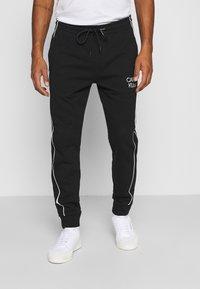 Calvin Klein - TWO TONE LOGO PANT - Tracksuit bottoms - black - 0